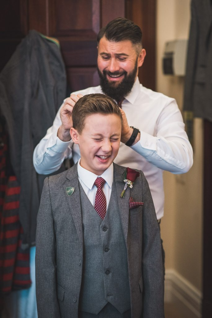 Second photographer captures groom prep as groom gets his best man ready