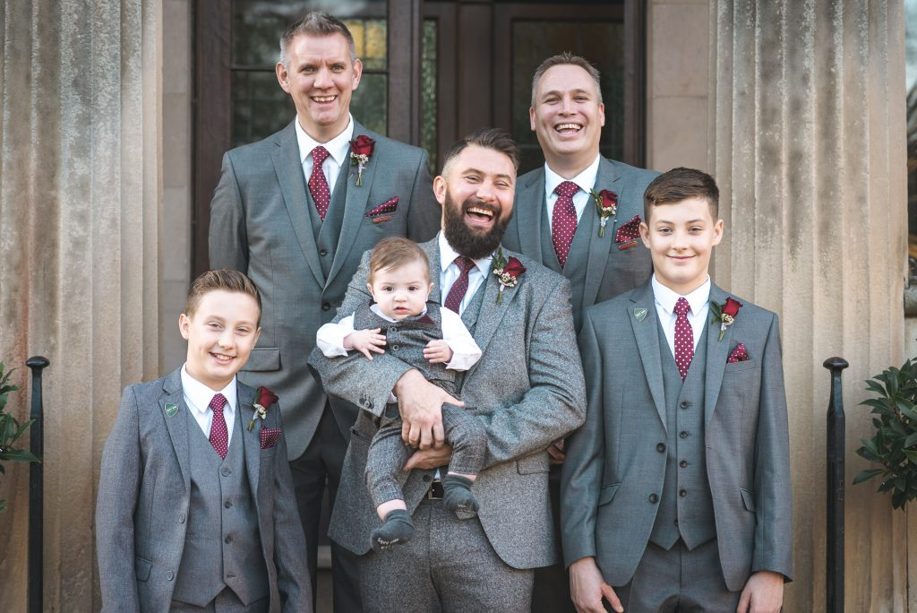 Groom and his groomsmen laugh whilst posing for their wedding photographer